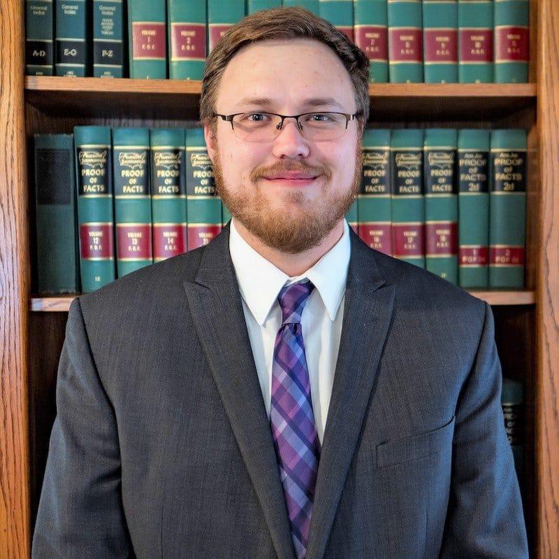 portrait photo of Austin Hiatt in front of his law firm's bookshelf